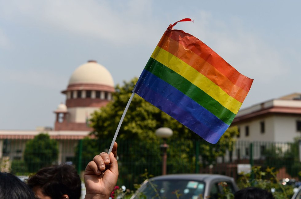 A boy waves the LGBT flag in New Delhi after hearing the ruling of the Indian Supreme Court.