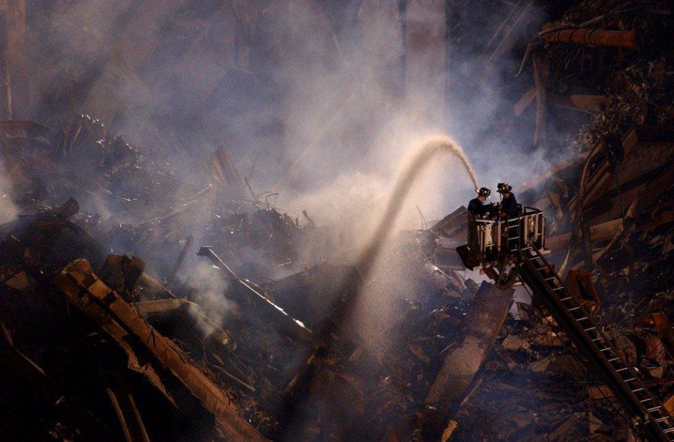 I pompieri spruzzano acqua con parte delle rovine delle Twin Towers il 2 ottobre 2001.