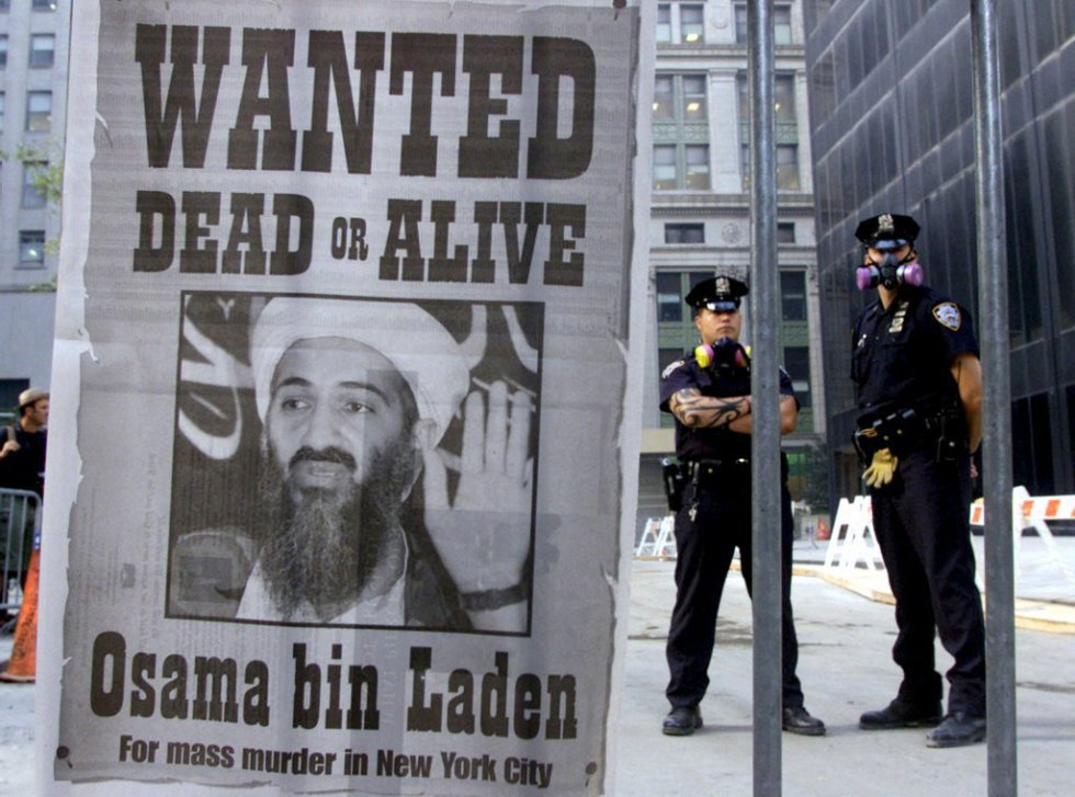 "Due poliziotti accanto a un manifesto distribuito da un quotidiano di New York, il 18 settembre, che chiede la cattura di Osama Bin Laden, con lo slogan ""Wanted dead or alive"", dopo l'attacco terroristico dell'11 settembre a le Twin Towers di New York e il Pentagono, a Washington."
