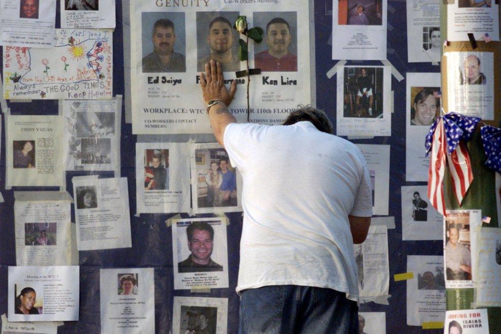 Un uomo si lamenta nel muro esterno del Bellevue Hospital di New York (USA), pieno di fotografie di persone scomparse negli attacchi terroristici contro le Twin Towers, quartier generale del World Trade Center.