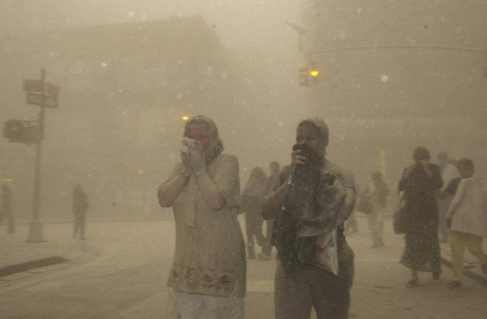 Diversi cittadini sembrano coperti di polvere mentre fuggono dall'area dopo il crollo delle Twin Towers.