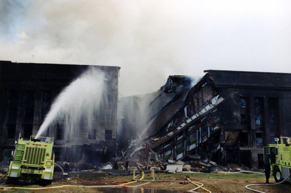 I vigili del fuoco cercano di estinguere l'incendio che è iniziato dopo che il volo 77 della American Airlines ha colpito le strutture del Pentagono.