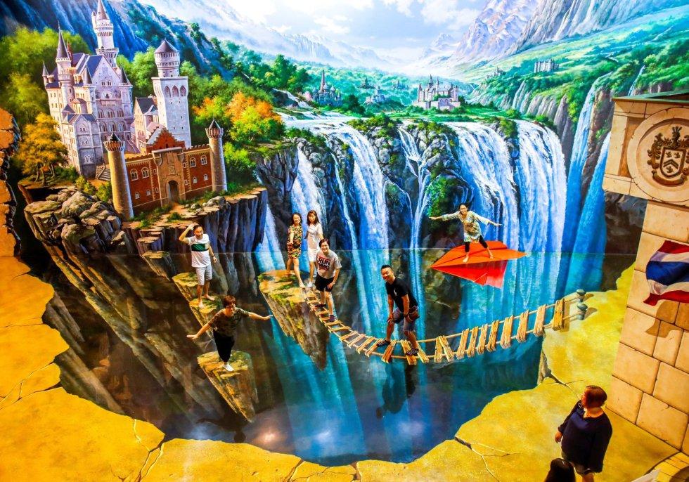 Varias personas posan en una de las pinturas de la exposición.
