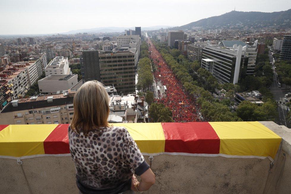 Una mujer observa desde un balcón la manifestación independentista.