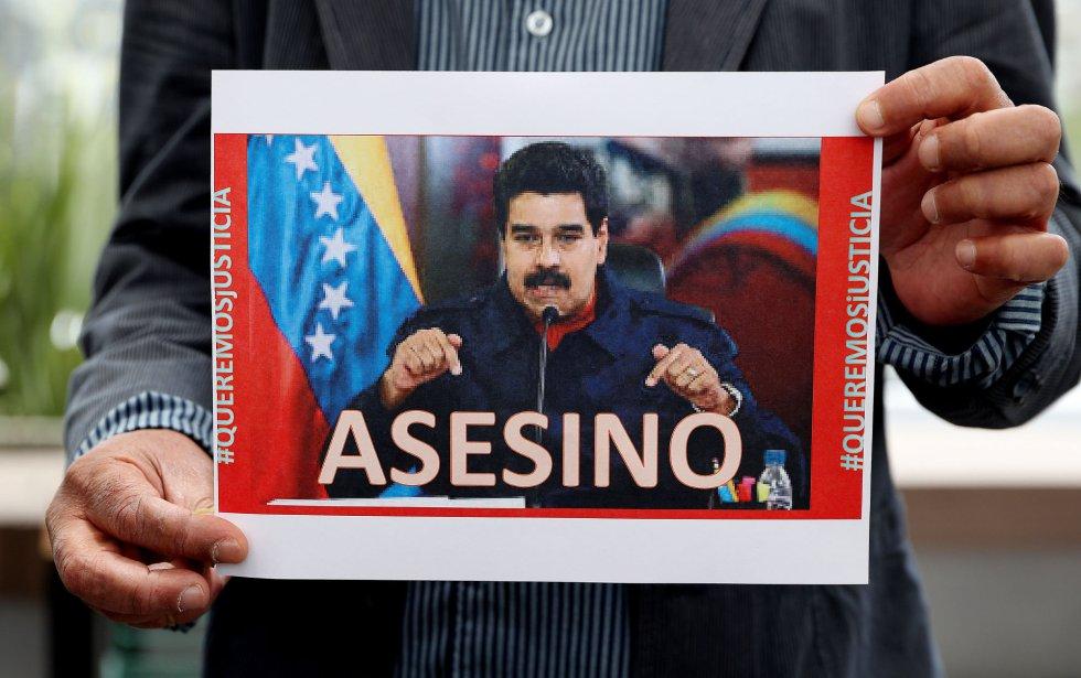 """Un hombre sostiene una fotografía del presidente de Venezuela Nicolás Maduro en la que se lee la palabra """"Asesino"""", mientras un grupo de dirigentes venezolanos, encabezados por el Concejal del estado Táchira, Simón Gamboa, se reúnen para rechazar la muerte del concejal venezolano Fernando Albán, en Bogotá (Colombia)."""