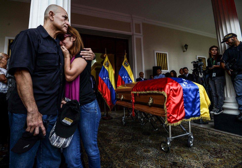 Miembros del partido opositor venezolano lloran durante la entrada del ataúd al edificio de la Asamblea Nacional.