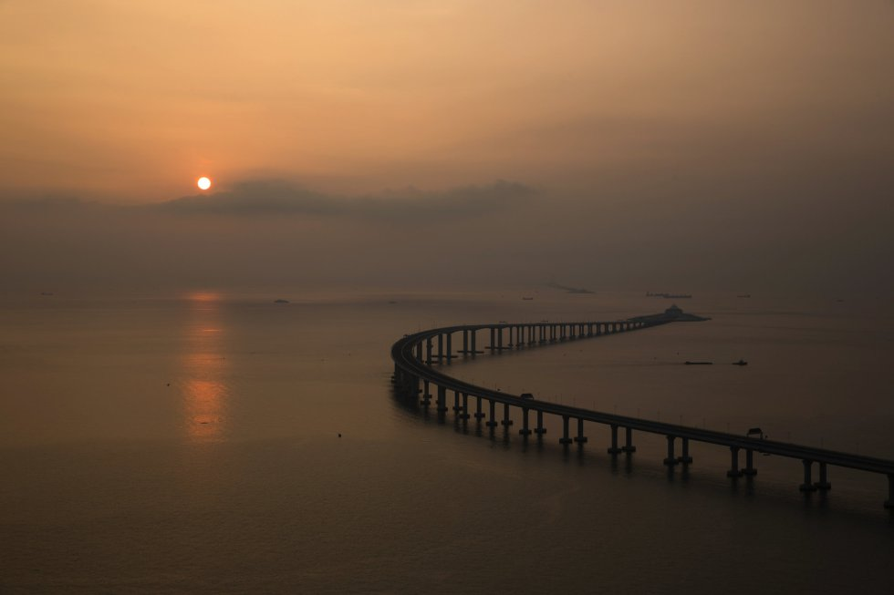 La obra, con un coste de más de 16.000 millones de euros, ha sido financiada por los gobiernos chino, de Hong Kong y de Macao. En la imagen, el sol del atardecer ilumina la infraestructura.