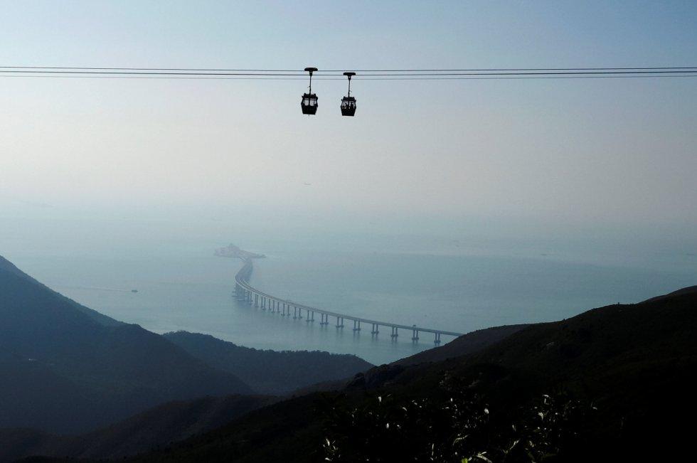 Se han empleado 400.000 toneladas de acero, 60 veces las utilizadas para construir la torre Eiffel, además de más de un millón de metros cúbicos de hormigón. El puente cuenta con una estructura principal de 29,6 kilómetros que constan de una sección de 22,9 kilómetros sobre el mar y otra de 6,7 de túnel submarino. En la imagen y en un primer plano, dos cabinas avanzan por el teleférico situado encima de la isla de Lantau, en Hong Kong, con el puente al fondo.