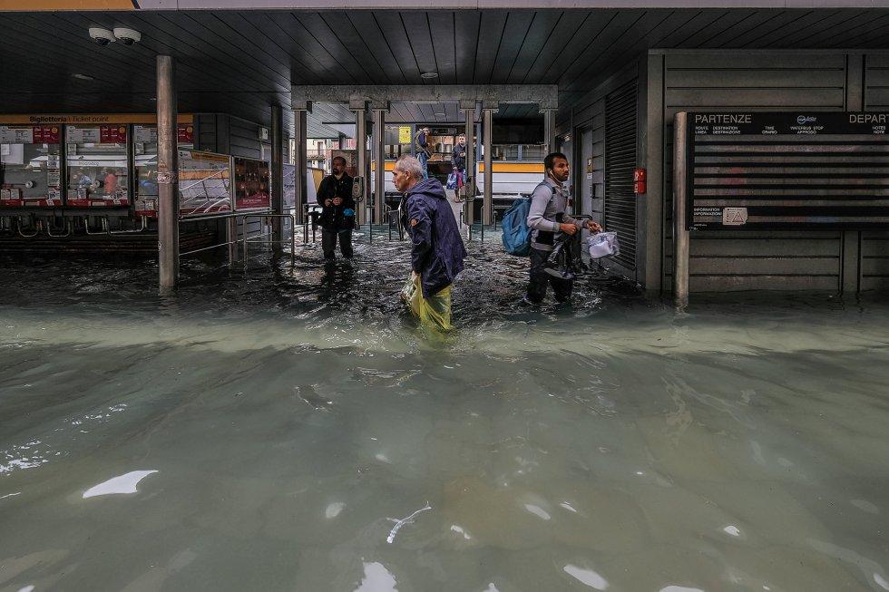 Varios viandantes intentan caminar frente a la estación del transbordador en Venecia. Además de las inundaciones, los fuertes vientos del temporal han provocado la caída de decenas de árboles en toda Italia.