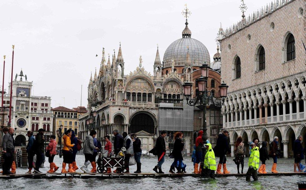 Los peatones transitan sobre pasarelas provisionales para cruzar la plaza San Marcos durante la marea alta, este lunes en Venecia.