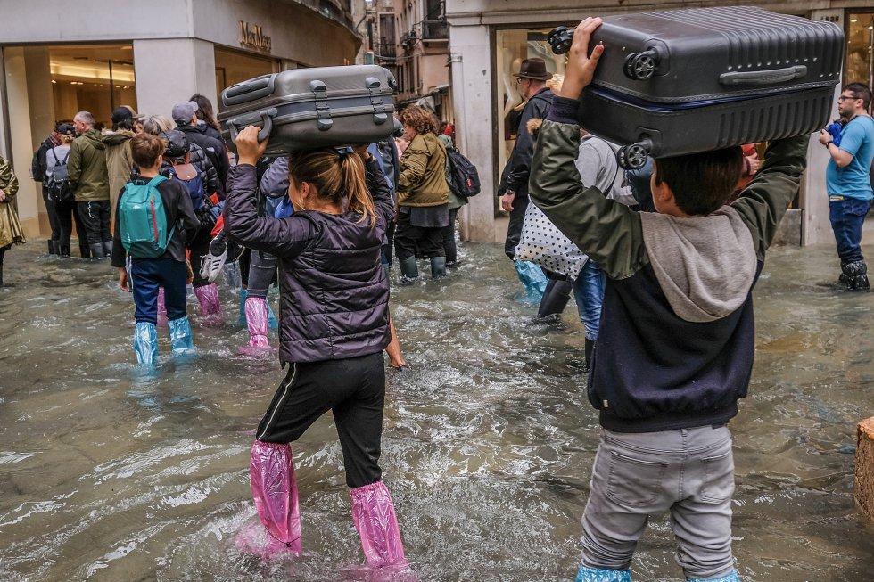 Los turistas cruzan las calles de Venecia con el equipaje sobre sus cabezas y con protectores plásticos hasta las rodillas para intentar no mojarse con el agua que en algunas zonas ha alcanzado los 156 centímetros.