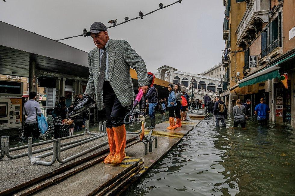 Un señor camina por las pasarelas temporales en Venecia tras la inundación causada por la marea alta, fenómeno que se conoce como 'acqua alta', en esta ocasión ha subido hasta los 156 centímetros, cifra que no se alcanzaba desde 2008.