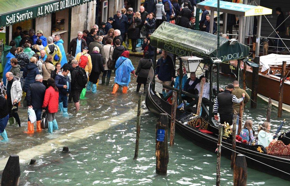 Los turistas caminaban por las calles inundadas de Venecia, este lunes 29 de octubre. Los meteorólogos preven una cierta mejora. En las últimas 48 horas se han registrado más de 7.000 operaciones de rescate en toda Italia.
