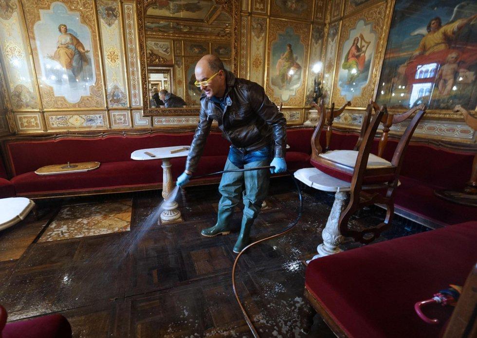 Un trabajador limpia, este martes, con una manguera el suelo de madera del histórico histórico Caffè Florian, en la plaza de San Marcos de Venecia.