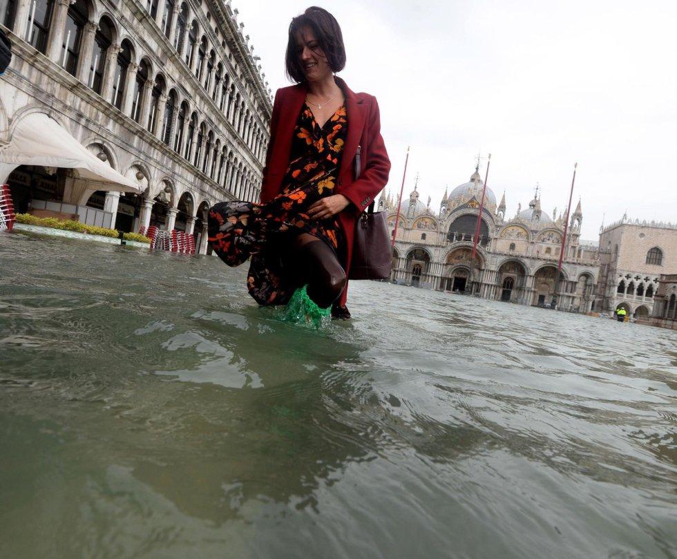 Una turista pasea por una inundada plaza de San Marcos en Venecia.