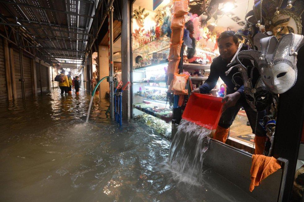 Un tendero achica agua de su tienda en Venecia.
