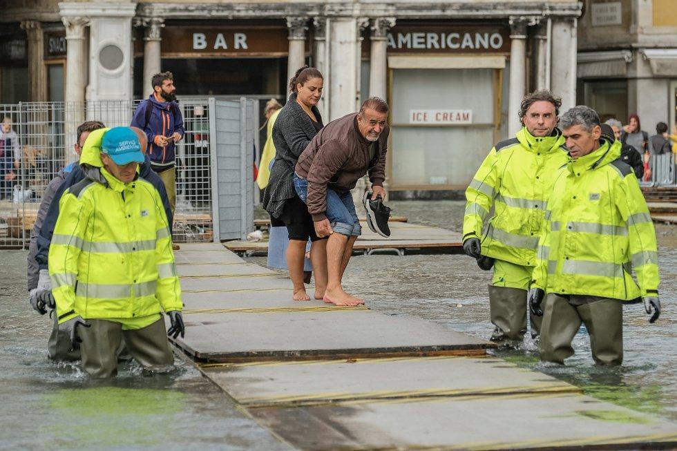 Un grupo de trabajadores colocan paneles de madera para facilitar el paso de turistas y locales, en Venecia.