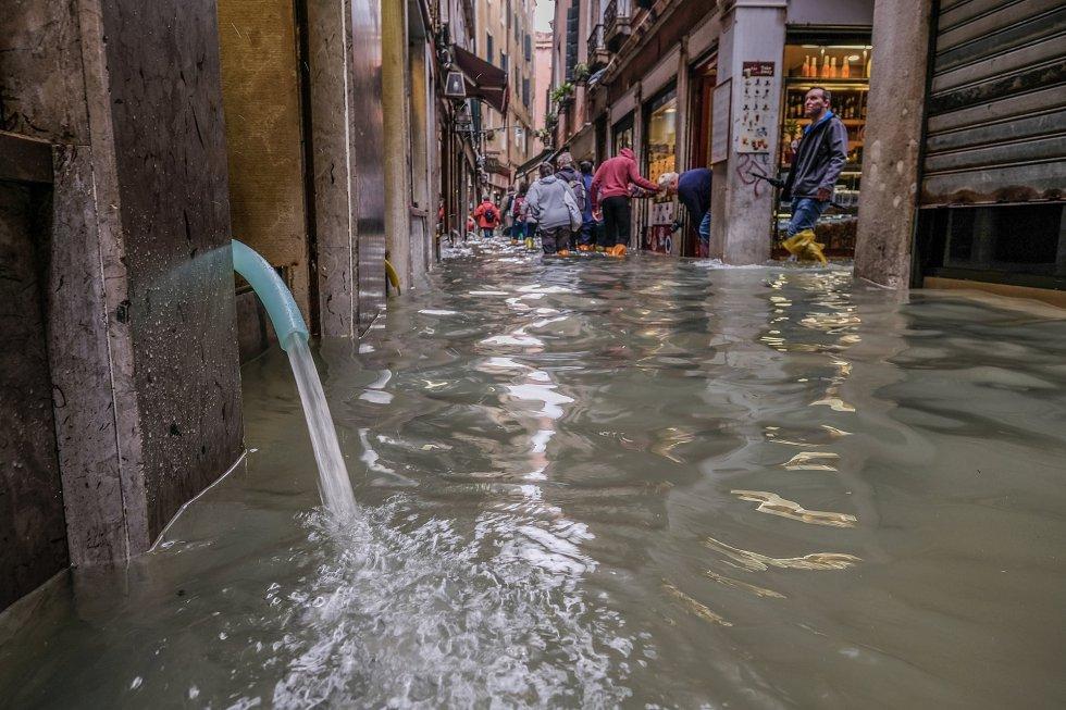 Un tubo drena agua mediante una bomba eléctrica en una tienda de Venecia.