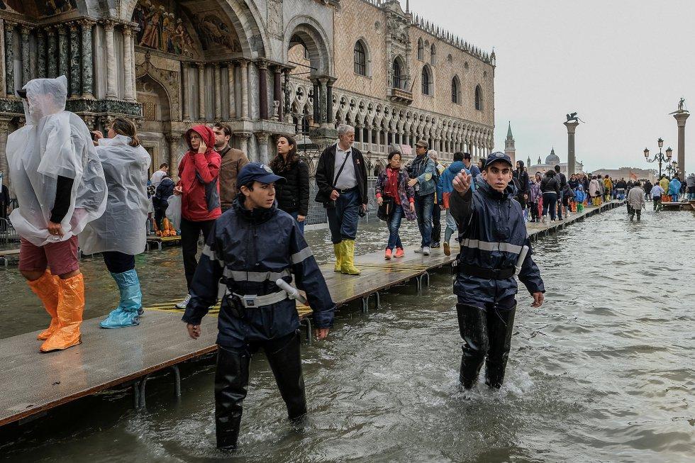 Dos policías locales comienzan la evacuación de la plaza de San Marcos de Venecia con motivo de la subida del nivel del agua.