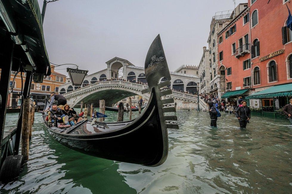 Un grupo de turistas se sube a una góndola a pesar del aviso de subida del agua en Venecia.
