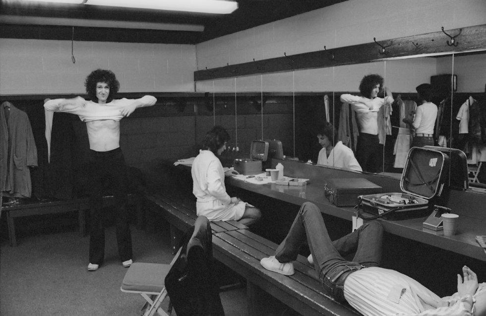 """Por que é tão boa.  Porque com esta canção nasceu o rock de estádio. Surpreendentemente curta (só dois minutos: achava que era mais longa?), mais básica impossível (inclusive poderia sobrar o solo de guitarra final) e de uma eficácia automática. Se alguém sonha em compor uma canção para coroar o mundo, está perdendo tempo: ela existe desde 1977.    A história da canção.  A maioria dos sucessos do Queen foram compostos por Mercury. Este não: leva a assinatura do guitarrista Brian May. Em que se inspirou para compor este clássico dos estádios? Em um estádio. Fala May: """"Uma noite, ao final de um show, nos retiramo do palco e de fundo escutei as pessoas cantando a música que entoa a torcida no estádio do Liverpool, 'You'll never walk alone'. Fui para a cama pensando em uma canção onde o público pudesse participar. São pessoas que estão ali, apertadas, mal podem se mover, mas podem aplaudir, bater seus pés e cantar. Quando acordei pela manhã 'We will rock you' saiu de puxão"""". Na imagem, o autor do tema, Brian May, vestindo-se no camarim para um show do Queen. Sentado, em frente ao espelho, Mercury.    Escute a canção  aqui ."""