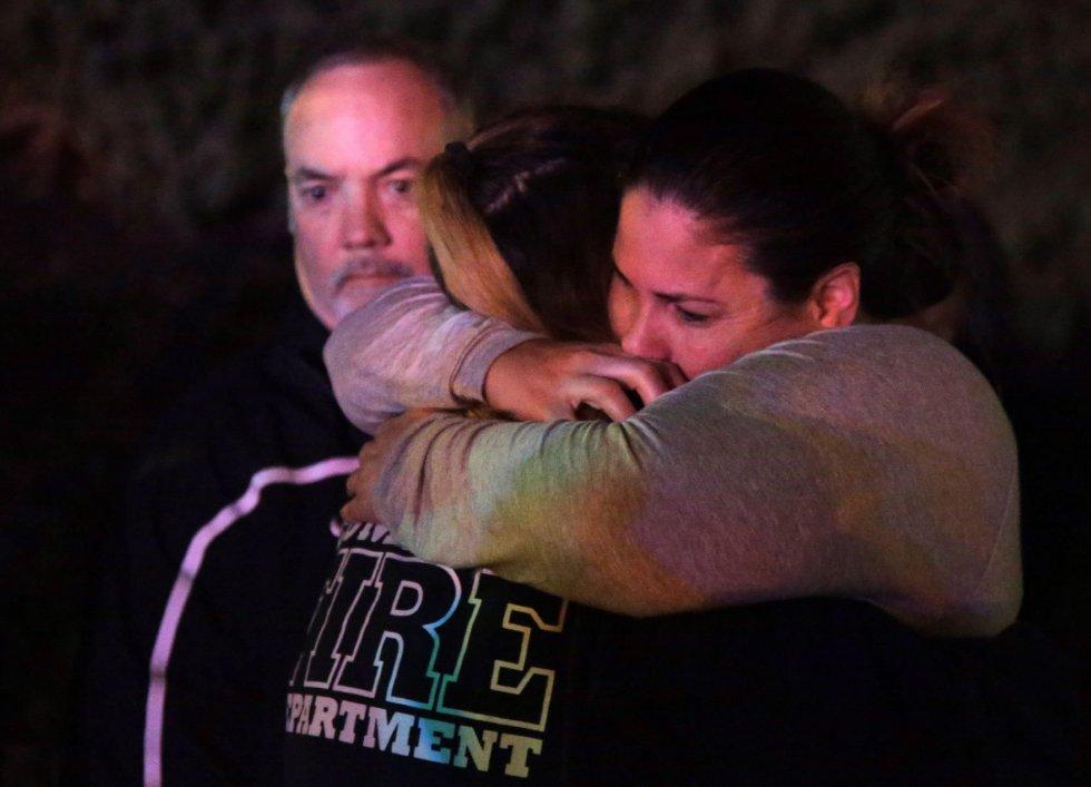 Una mujer que ha huido del lugar del tiroteo, en el Borderline Bar and Grill, abraza a sus familiares en la localidad de Thousand Oaks.