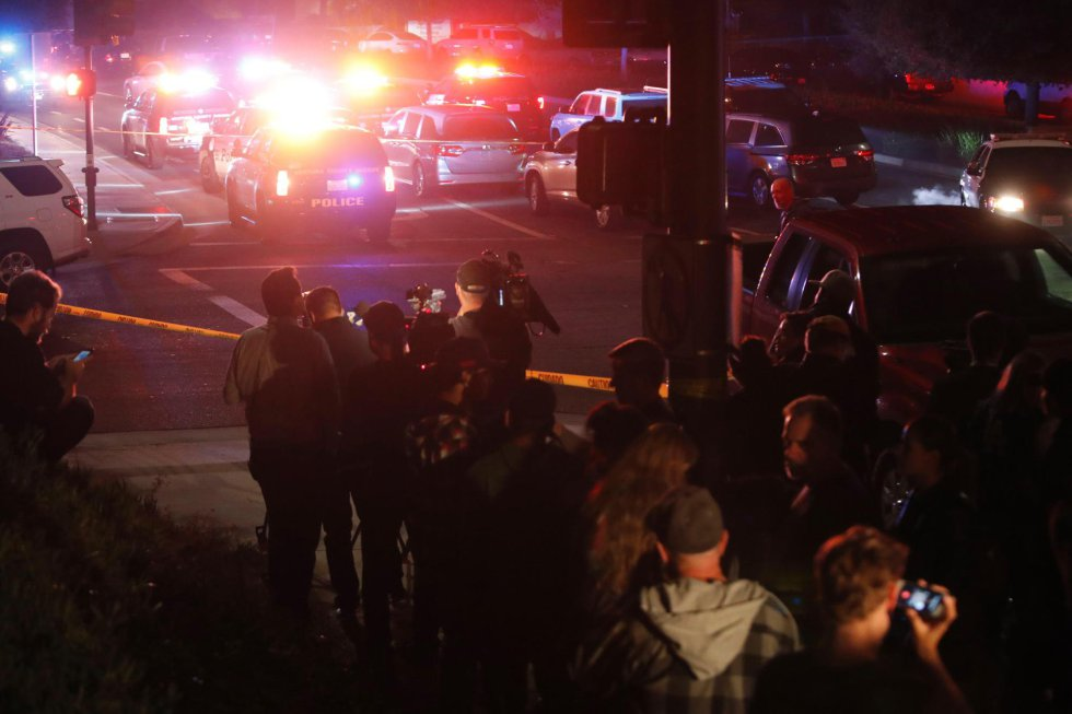 Un grupo de gente y prensa se agrupa cerca del lugar del tiroteo.