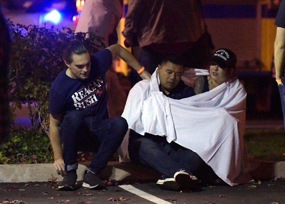 Un grupo de jóvenes se consuelan, sentados en las proximidades del tiroteo.