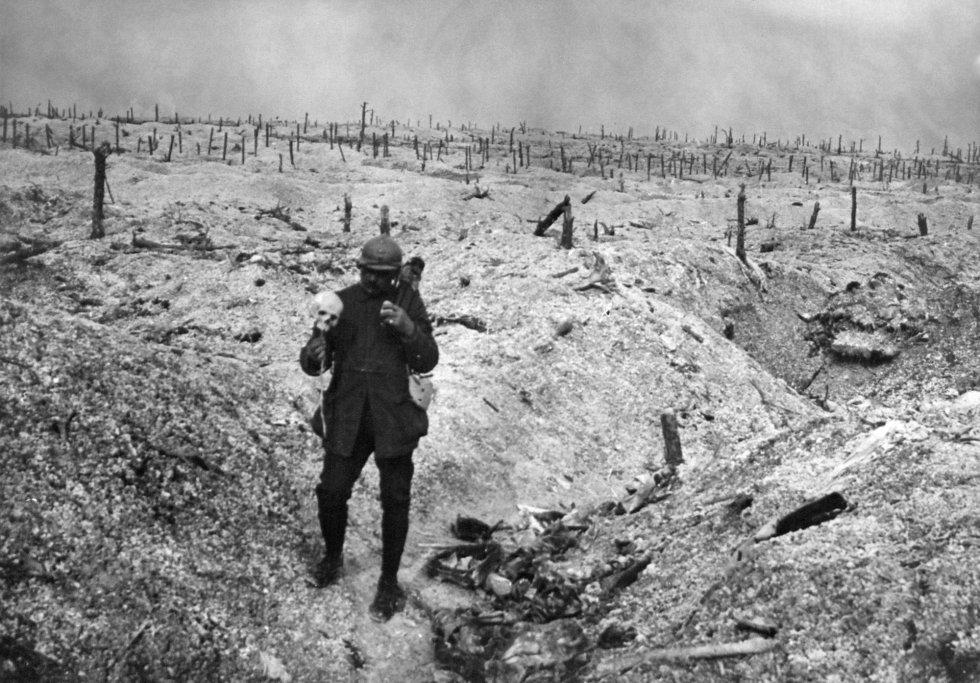 Imagen de la Biblioteca Internacional de Documentación Contemporánea (BDIC) que muestra a un soldado francés sosteniendo un cráneo humano en medio de una zona de trincheras devastada por los bombardeos.