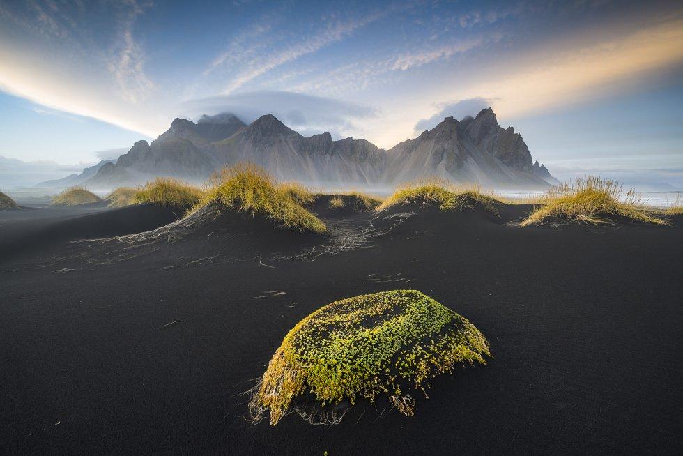 Esta praia do sul da Islândia tem um singular sistema de dunas de areia vulcânica coroadas pelo afiado perfil das montanhas costeiras. Aqui, com a luz do céu de um entardecer outonal.