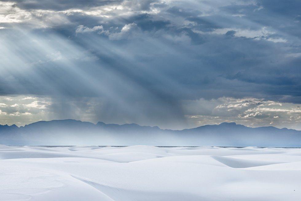 Uma enorme nuvem descarrega chuva torrencial sobre as montanhas de San Andrés, que rodeiam as dunas do White Sands National Monument, nos Estados Unidos. Sua areia confunde-se com a neve devido a sua extrema brancura.