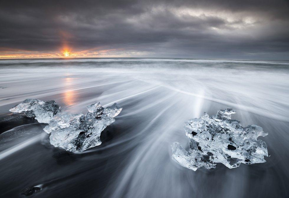 O sol sobe presenteando a única nota de cor a uma manhã em que pedaços de gelo glacial são varados em uma praia de areia vulcânica no sul da Islândia.