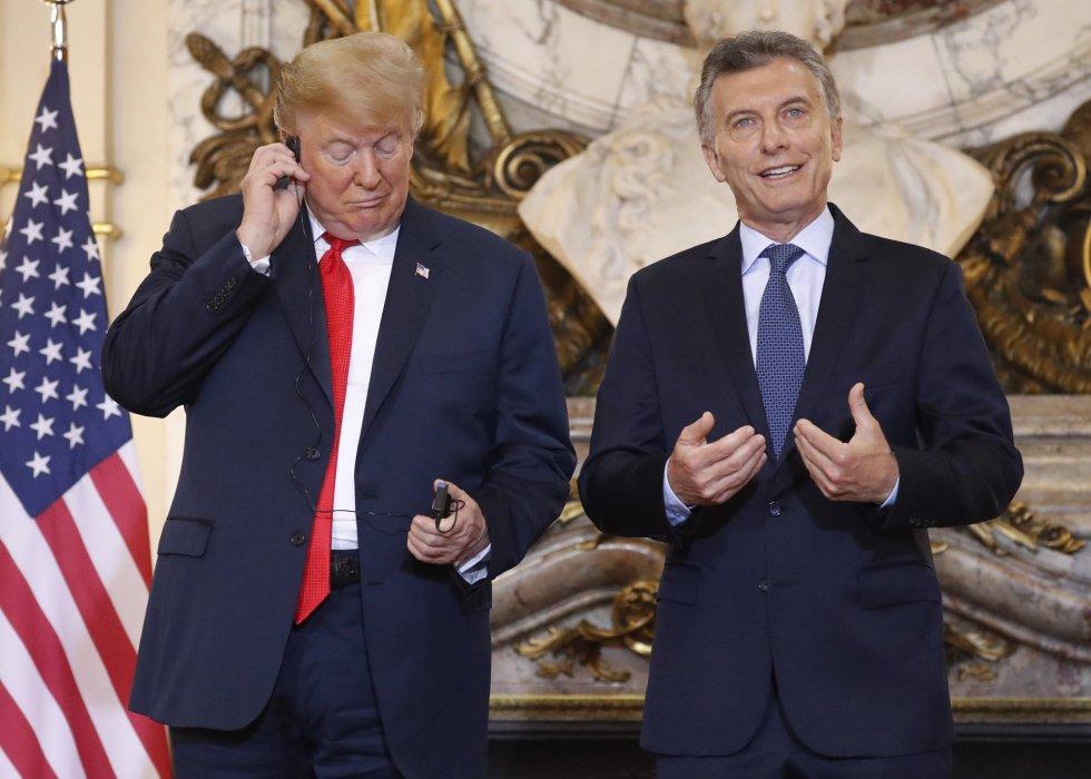 Donald Trump comprueba el audífono con el que escucha la traducción de las declaraciones de Mauricio Macri en la Casa Rosada.