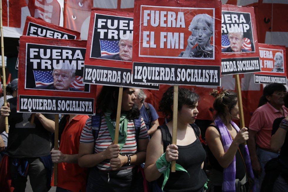 """Manifestantes portan pancartas en las que se puede leer """"Fuera el FMI"""", """"Fuera Trump"""" durante una concentración en Buenos Aires, por la reunión del G20 en Argentina, el 30 de noviembre de 2018."""