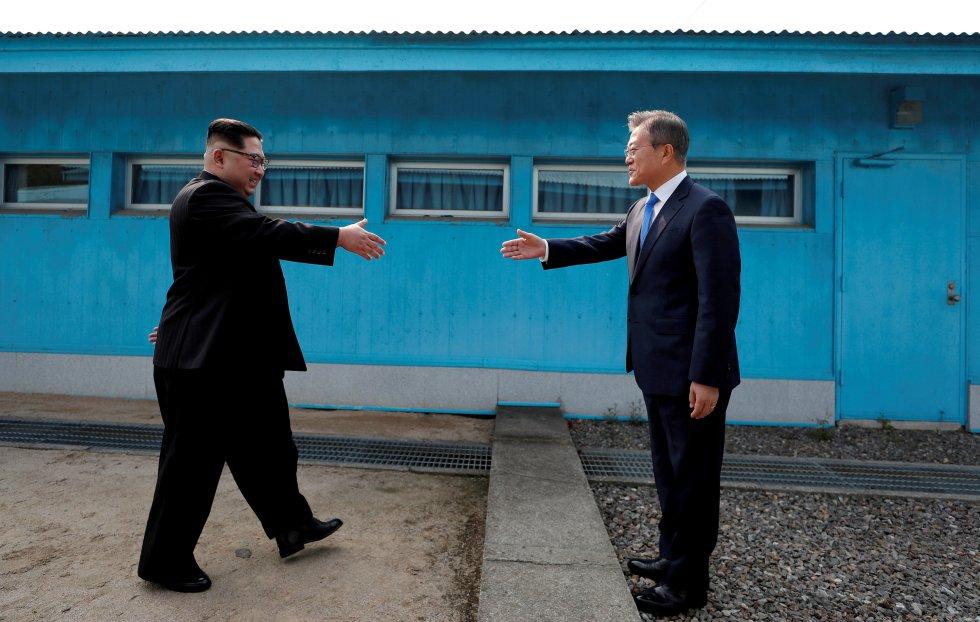 El presidente de Corea del Sur, Moon Jae-in, y su homólogo de Corea del Norte, Kim Jong Un, estrechan sus manos en Panmunjom, dentro de la zona desmilitarizada que separa a las dos Coreas, el 27 de abril de 2018. La tercera cumbre que se celebra entre los dos países estuvo cargada de simbolismo, incluyendo la mesa en la que se sentaron los líderes, de 2.018 milímetros de ancho, para marcar el año.