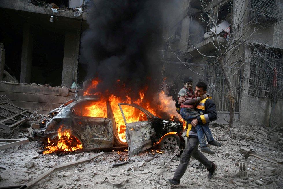 Un miembro de la defensa civil de Siria lleva en brazos a un niño herido tras un ataque aéreo del régimen de Al Asad sobre la ciudad de Hamoria, al este de Guta, el 6 de enero de 2018. Según el Observatorio Sirio de Derechos Humanos, una ONG con sede en Londres que monitoriza el conflicto de aquel país, los ataques aéreos y el fuego de artillería del Ejército sirio dejaron un saldo de 24 personas fallecidas, incluidos 10 menores. Desde que se desataron las hostilidades en 2011, la guerra siria se ha cobrado la vida de más de 500.000 personas.