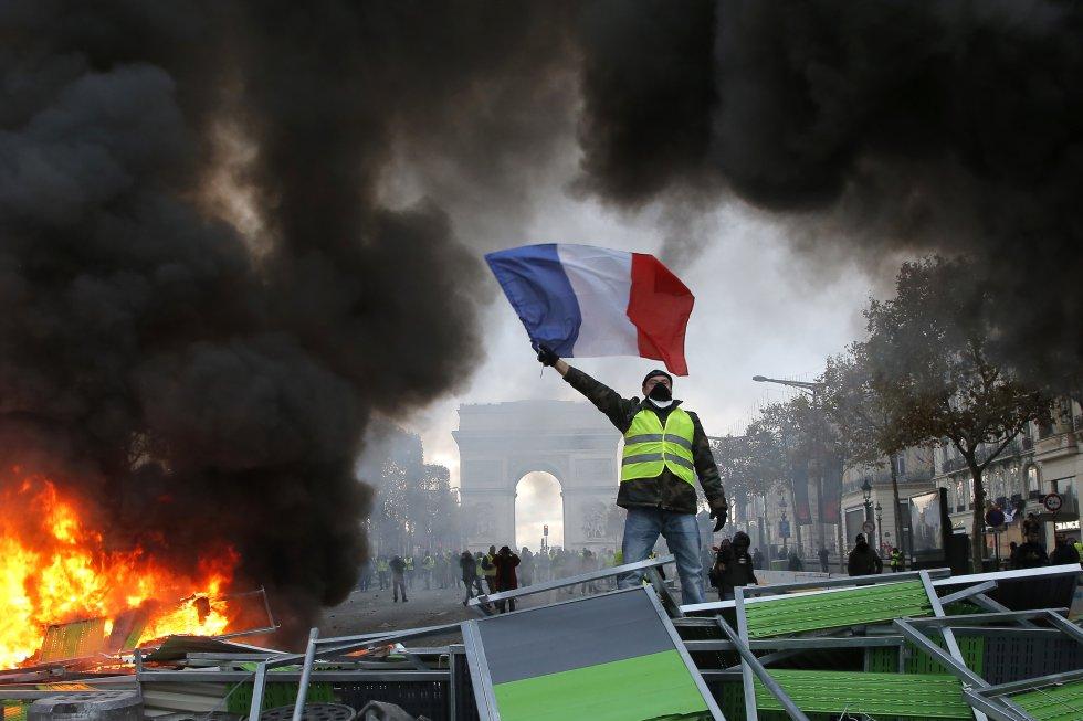 Un manifestante ondea la bandera de Francia mientras participa en la protesta de los 'chalecos amarillos' en París (Francia), el 24 de noviembre de 2018. Al fondo de la imagen, el Arco de Triunfo. Con una agenda inicial que buscaba la supresión del aumento de la tasa al diésel y la gasolina, prevista para el 1 de enero, la revuelta consiguió que el Gobierno francés anulase la subida de la tasa al carburante y aprobase ayudas de 10.000 millones de euros para reforzar el poder adquisitivo.
