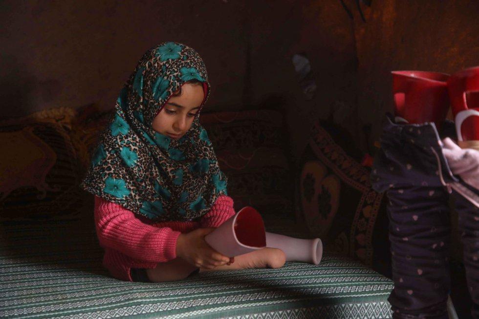 Hoje, a menina pode caminhar graças a suas novas próteses após se submeter a um tratamento na Turquia. Nessa imagem, Maya observa suas pernas ortopédicas já em sua casa dentro do acampamento para refugiados internos em que vive. Como a família Merhi, o conflito sírio deixou mais de 11 milhões de pessoas desabrigadas, aproximadamente a metade dentro da Síria e metade como refugiadas no estrangeiro, incluindo mais de 3,5 milhões na vizinha Turquia.