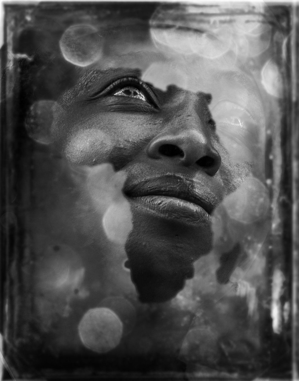 'A través del cristal' es la imagen ganadora de un accésit en la edición de 2016 del concurso Africanas en España y su autor es Javier Domínguez 'Jadoga' (Jérez de la Frontera, 1982), un veterano fotógrafo y formador en esta disciplina especializado en fotografía publicitaria, retrato y edición avanzada. En un correo electrónico, Jadoga explica que la protagonista de su imagen es Victoria, conocida de una amiga de Jerez. Nació en Nigeria y reside con sus tres hijas en la ciudad gaditana, donde posee su propio negocio de venta de ropa.    Esta toma tan original fue realizada fusionando dos imágenes, según explica el autor: