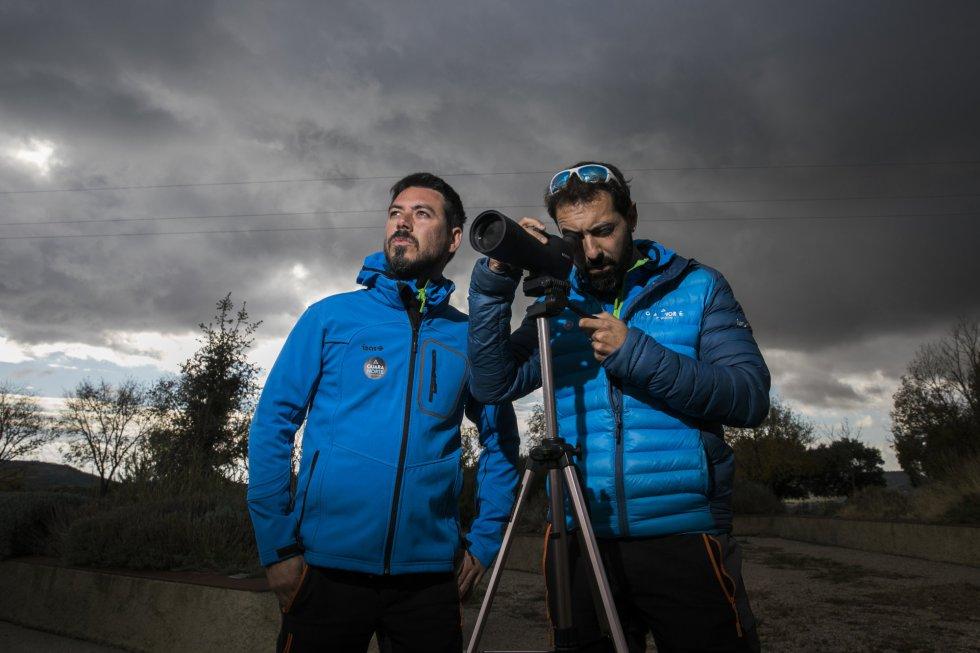 Adrián Navarro (izquierda) y Belián Martínez, promotores de la empresa de turismo de aventura Guara Norte, observan aves desde las instalaciones del centro de interpretación de Nueno. Debido a la mala conexión de Internet del municipio se han visto obligados a operar su negocio desde Huesca.