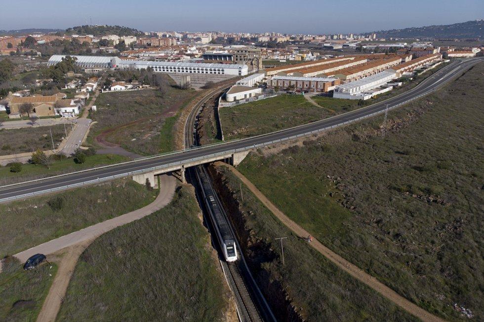 El proyecto de la alta velocidad extremeña se divide en tres tramos: Madrid-Oropesa, Oropesa-Plasencia y Plasencia-Badajoz. Se presupuestó en 3.350 millones. Zapatero dijo que estaría listo en 2010. Rajoy, que en 2015. La realidad es que el primer recorrido se encuentra en estudio; del segundo solo se ha ejecutado un 18%: 154 millones de los 823 presupuestados. Y del tercero, el más avanzado, el 75,6%; 1.065,6 de los 1.407 estimados. En la imagen, un tren circula por la vía ferroviaria que une Cáceres (al fondo) y Badajoz, bajo la carretera nacional EX-100.