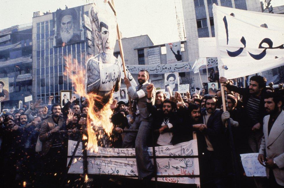 El exilio del Sha y el regreso de Jomeini no puesieron fin a las protestas. En la foto, domada en algún momento de 1979, un grupo de manifestantes quema una imagen de Mohammad Reza frente a la Embajada de EEUU en Teherán, nuevo objetivo de las protestas. El malestar por el apoyo de Washington al monarca alentará la toma de la Embajada norteamericana por un grupo de estudiantes en noviembre de ese mismo año. Los asaltantes, con el aparente respaldo de los nuevos líderes, mantuvieron secuestrados a 52 diplomáticos durante 444 días. La crisis, que se tradujo en la ruptura de relaciones, dura hasta hoy.