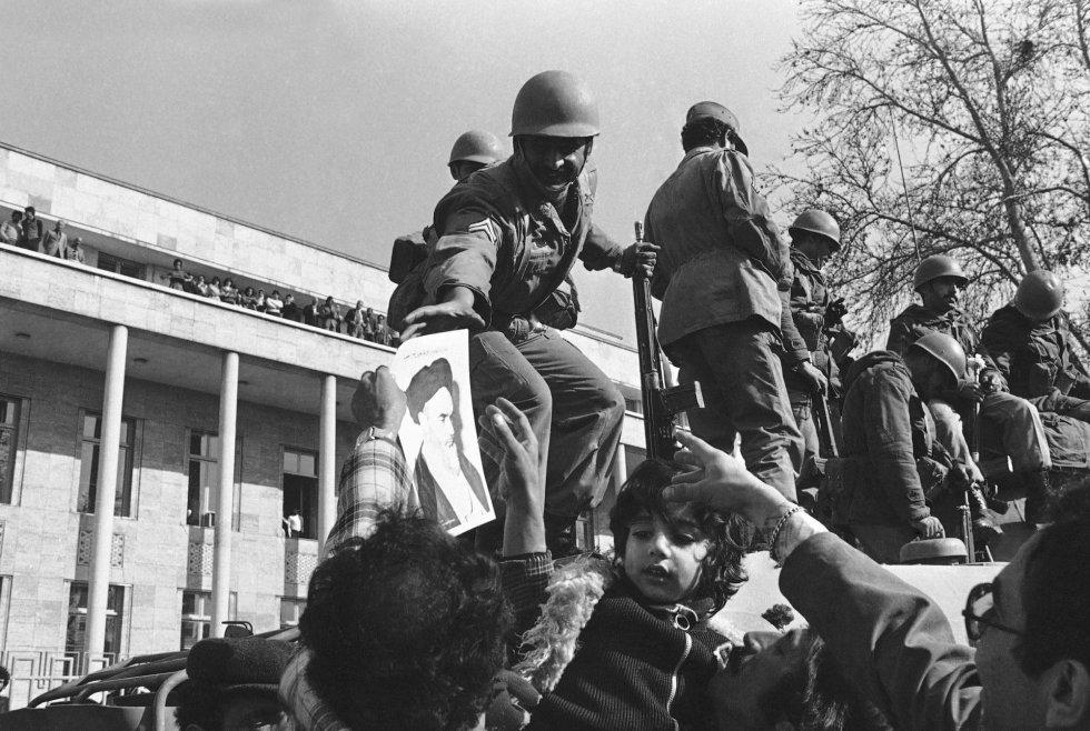 Los manifestantes entregan fotos de Jomeini y flores a los soldados frente a un edificio sin identificar en el centro de Teherán. La foto se tomó a mediados de enero de 1979. Aunque muchas de las manifestaciones se reprimieron con violencia, también hubo momentos de confraternización entre quienes protestaban contra el Sha y quienes tenían el deber de defender la monarquía.