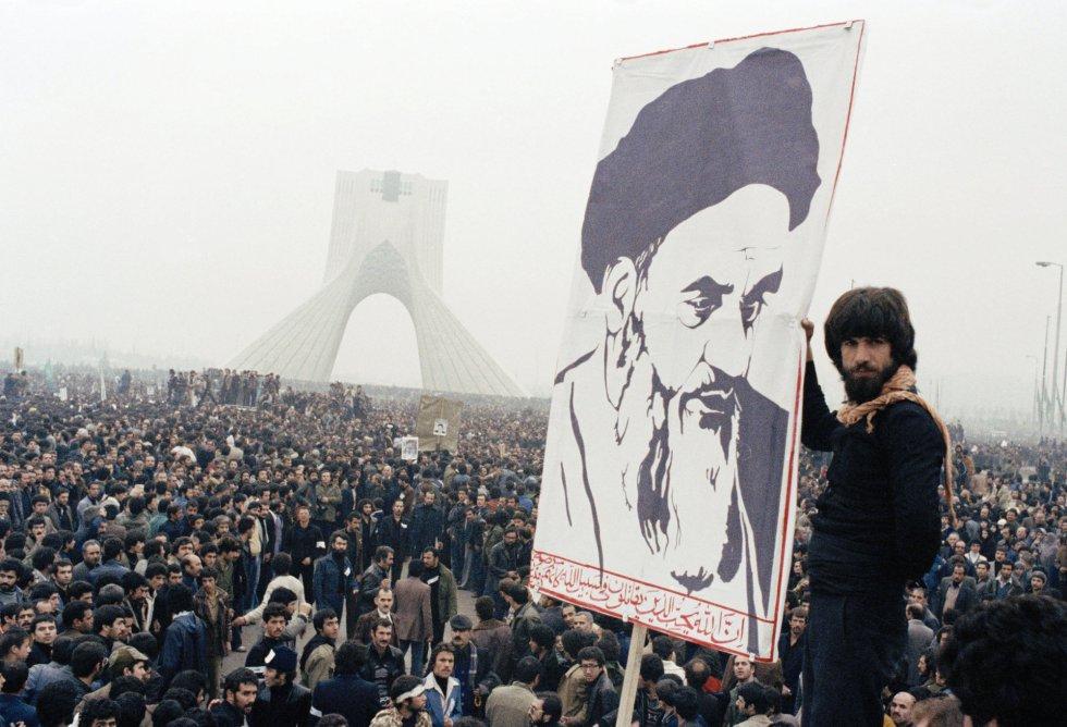 """Un manifestante sujeta un retrato del ayatolá Jomeini, un oscuro clérigo a quien el Sha envió al exilio y que, primero desde la ciudad iraquí de Nayaf y luego desde París, logró convertirse en el símbolo de la revolución que se gestaba. Sus sermones, difundidos a través de cintas de casete, prepararon el terreno no sólo para el cambio de régimen, sino para una forma de gobierno, la """"república islámica"""", que no tenía precedentes."""