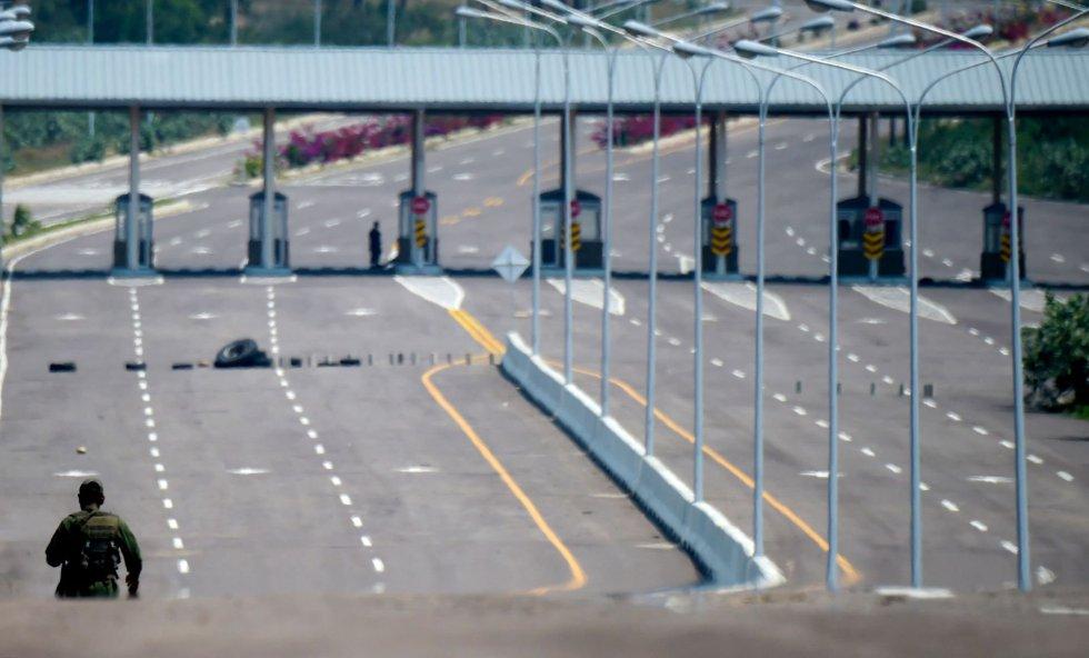 """Un militar venezolano monta guardia en el bloqueo del puente de Tienditas en la frontera. El envío de ayuda, a través de Colombia, Brasil y una isla del Caribe no concretada, es una iniciativa del presidente interino de Venezuela, Juan Guaidó, apoyada por Washington y Bogotá. Nicolás Maduro rechaza la ayuda al considerarla tanto una """"agresión"""" como una excusa para una intervención en Venezuela."""