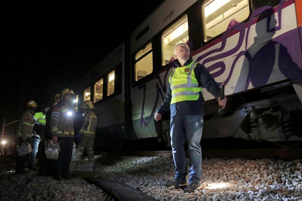Bomberos trabajan en la zona del accidente de trenes de Barcelona, este viernes por la noche.