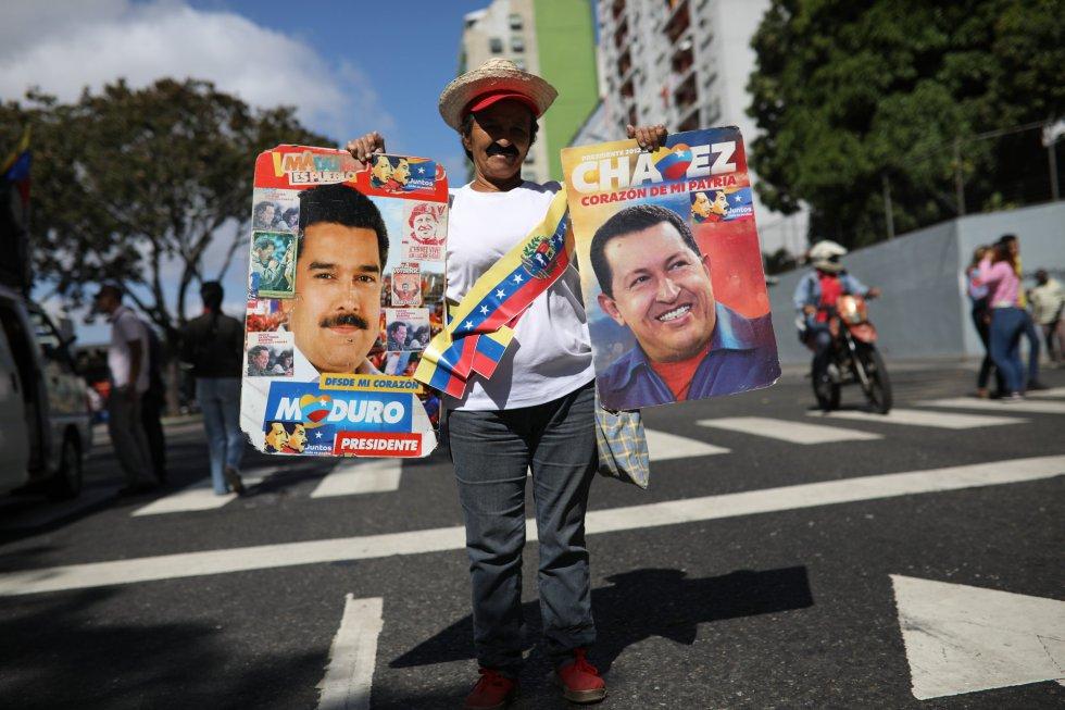 Ana Castellanos, partidaria del chavismo, sostiene imágenes de Nicolás Maduro y de Hugo Chávez en el transcurso de la manifestación a favor del Gobierno en la capital venezolana.