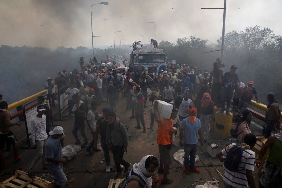 Miembros de la oposición descargan la ayuda humanitaria de un camión que fue incendiado sobre el puente Francisco de Paula Santander, en la frontera entre Colombia y Venezuela.