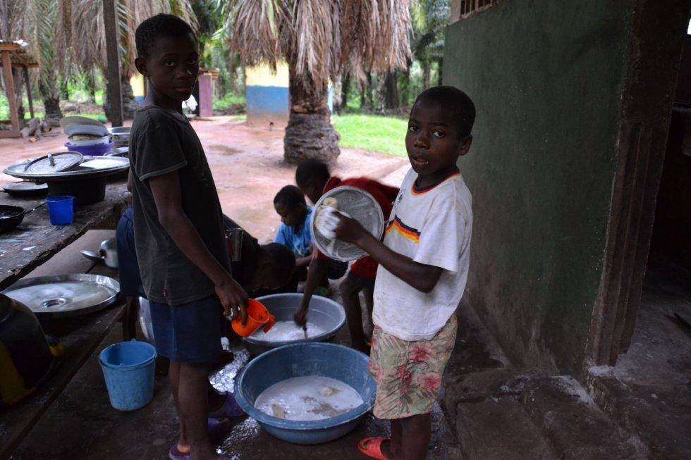 Niños del Hogar Infantil ayudan a lavar los platos y ollas de la cocina. Aquí es donde se mezclan con compañeros bantúes y los dos grupos étnicos aprenden a convivir. A pesar de las dificultades iniciales que supuso esto, se ha conseguido que crezcan juntos y aprendan a respetarse.
