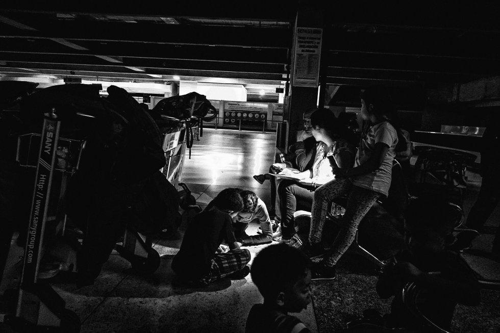 El jueves 7 de marzo a las 16.50 un apagón masivo dejaba sin luz a gran parte del país. Durante los siguientes días, muchos sectores de la capital, Caracas, estuvieron sin energía, incluido el aeropuerto de Maiquetía. En la imagen, varios pasajeros que llegaron el viernes rellenan hojas de reclamo.